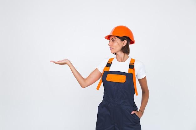 Hübsche ingenieurin beim bau von schutzhelmen auf weißem selbstbewusstem lächeln halten leeren raum auf der linken hand
