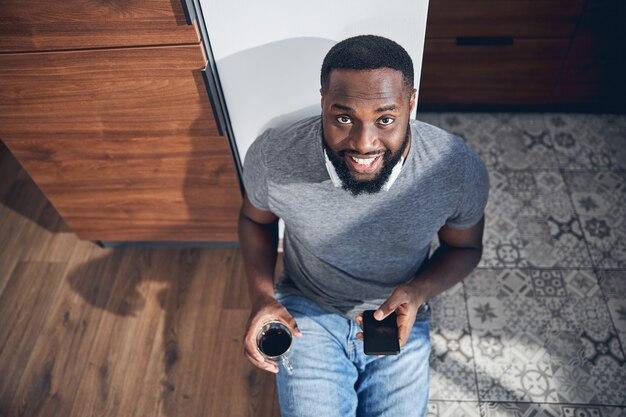Hübsche internationale männliche person, die sein lächeln zeigt, während sie auf dem boden sitzt und kaffee trinkt