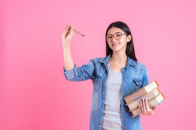 Hübsche jugendfrau des porträts, die bücher in ihrem arm hält und bleistift auf rosa, bildungskonzept verwendet