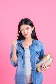 Hübsche jugendfrau des porträts, die bücher in ihrem arm hält und bleistift auf rosa verwendet