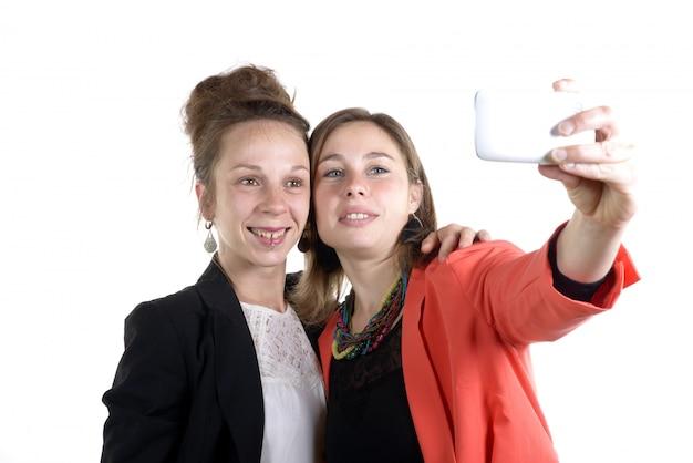 Hübsche jugendlich frauen, die selfies mit ihrem smartphone nehmen