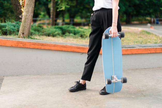 Hübsche jugendliche mit skateboard im rochenpark