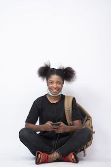 Hübsche junge afrikanische frau, die einen rucksack trägt, sitzende beine mit ihrem handy gekreuzt