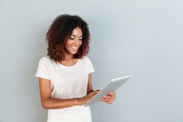 Hübsche junge afroamerikanische frau, die steht und tablette verwendet