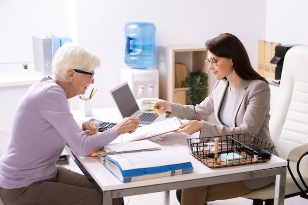 Hübsche junge agentin, die dem älteren kunden hilft, das versicherungsdokument auszufüllen, während beide am schreibtisch im büro sitzen