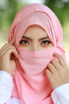 Hübsche junge asiatische arabische frau, die rosa hijab trägt, der in der grünen natur im freien zuversichtlich ist. porträt mit schönen muslimischen augen mädchen. sie berührte ihr gesicht und sah in die kamera. werbeporträt-konzept.
