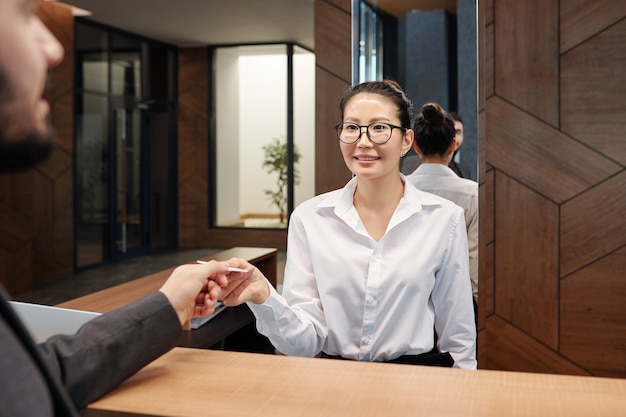 Hübsche junge asiatische empfangsdame, die karte vom hotelzimmer zum geschäftsreisenden über empfangsschalter übergibt