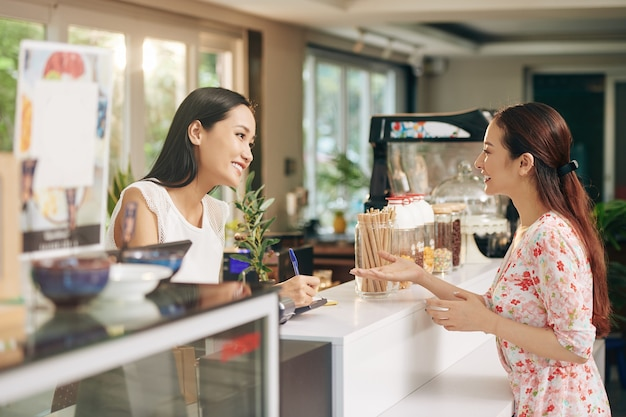 Hübsche junge asiatische frau, die mit barista spricht und kaffee und nachtisch bestellt