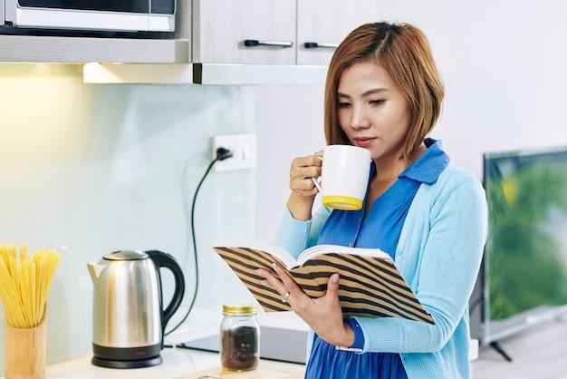 Hübsche junge asiatische frau, die morgenkaffee trinkt und buch in der küche liest