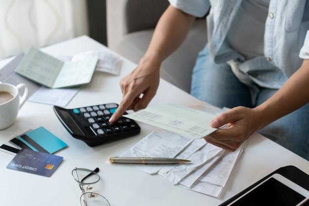Hübsche junge asiatische frau, die rechner verwendet, während bankbankbuch hält, um hauskosten und steuern im wohnzimmer zu hause zu berechnen.