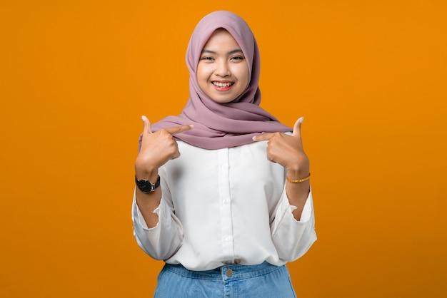 Hübsche junge asiatische frau, die sich auf gelb glücklich fühlt