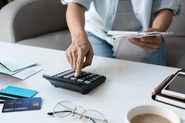 Hübsche junge asiatische frau, die taschenrechner verwendet, während rechnungen hält, um hauskosten und steuern im wohnzimmer zu hause zu berechnen.