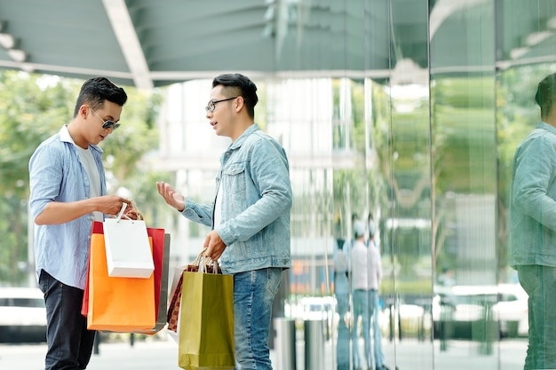 Hübsche junge asiatische männer mit einkaufstüten, die außerhalb des einkaufszentrums stehen und einkäufe besprechen