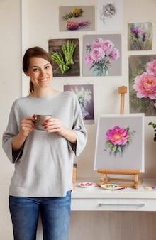 Hübsche junge barfüßige künstlerin in freizeitkleidung trinkt kaffee, während sie sich entspannt, nachdem sie eine skizze einer leuchtend rosa hagebutte geschrieben hat, die auf einem tisch auf einer staffelei und werkzeugen steht