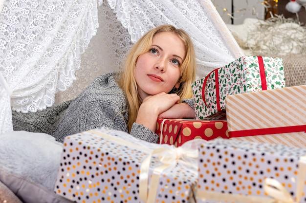 Hübsche junge blonde frau, die auf weihnachtsgeschenkkästen liegt, tragen weißen gestrickten pullover