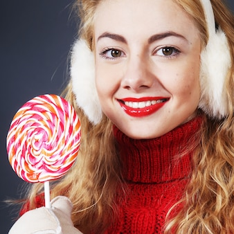 Hübsche junge blonde frau, die lollypop hält