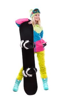Hübsche junge blonde frau im bunten schneemantel halten snowboard