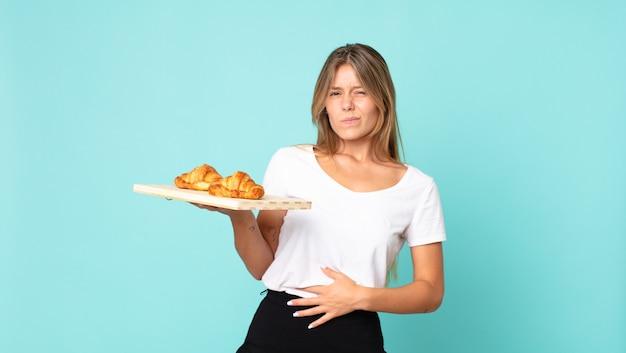 Hübsche junge blonde frau mit einem croissant-tablett