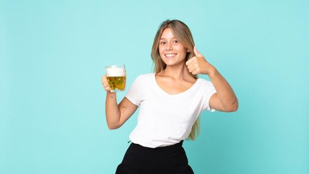 Hübsche junge blonde frau mit einem halben liter bier