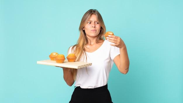 Hübsche junge blonde frau mit einem muffins-tablett