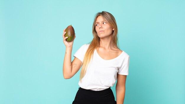 Hübsche junge blonde frau mit einer mango