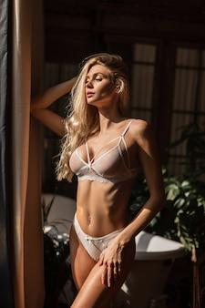 Hübsche junge blonde frau mit natürlichem schönheitsgesicht in sexy unterwäsche in einem raum im sonnenlicht. heiße weiße spitzenunterwäsche auf einem weiblichen schlanken körper mit großen schönen brüsten