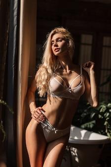 Hübsche junge blonde frau mit perfektem körper in sexy spitzenwäsche steht in einem badezimmer bei sonnenlicht. sinnliche unterwäsche neue kollektion