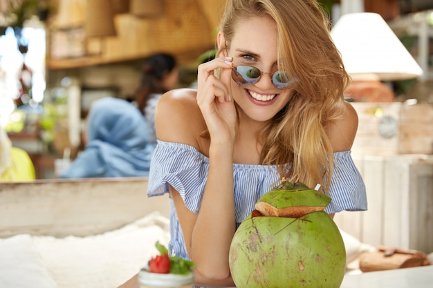 Hübsche junge blonde frau schaut durch sonnenbrille, posiert mit positivem ausdruck in der kamera, umgeben von exotischen cocktails, verbringt freizeit in exotischen cafés, probiert lokale gerichte und getränke