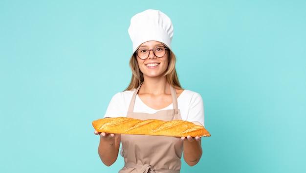 Hübsche junge blonde kochfrau, die ein brotbaguette hält