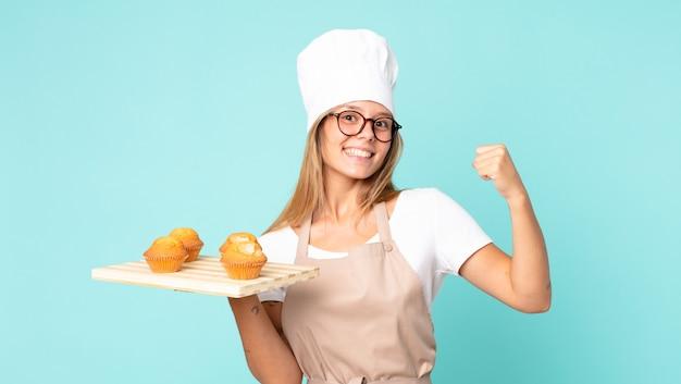 Hübsche junge blonde kochfrau, die ein muffinstablett hält