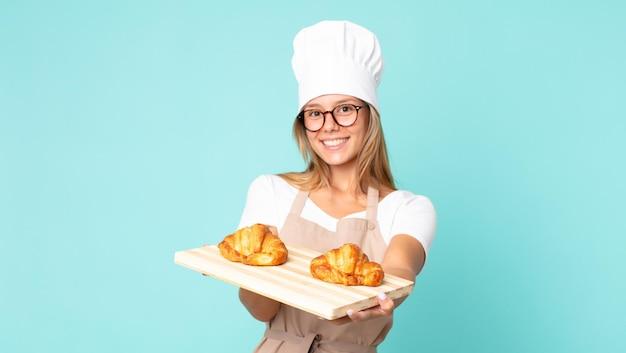 Hübsche junge blonde kochfrau, die ein tablett mit croissants hält