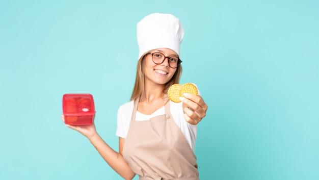 Hübsche junge blonde kochfrau und hält eine tupperware