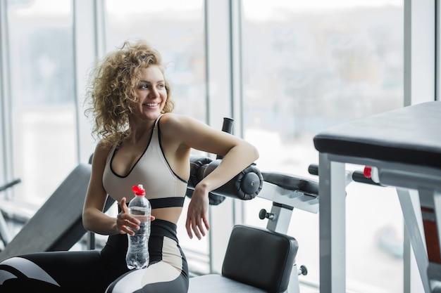 Hübsche junge blonde sportlerin, die sich nach dem training entspannt und wasser im fitnessstudio trinkt