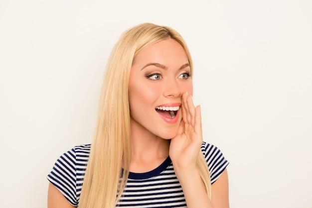 Hübsche junge blondine hält hand in der nähe des mundes und erzählt geheimnis