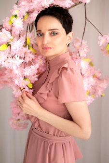 Hübsche junge brünette frau, die rosa kleid trägt, steht nahe ast, der mit rosa blumen blüht