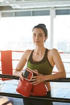 Hübsche junge brünette frau mit boxhandschuhen, die bereit sind, vor dem wettkampf sporttraining auf dem ring zu haben
