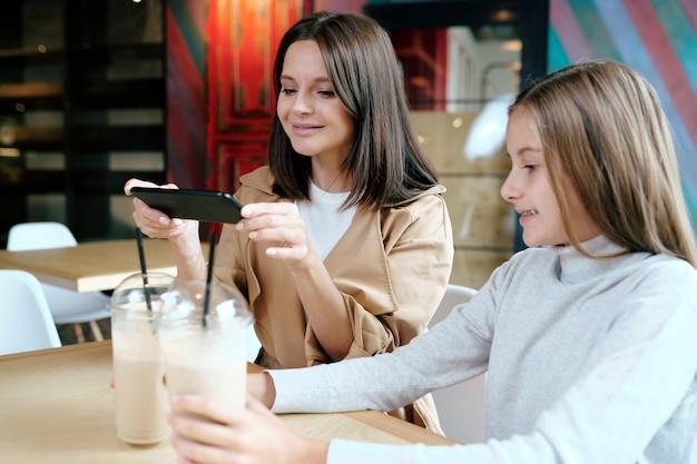 Hübsche junge brünette frau mit smartphone, die foto von zwei milchcocktails im café macht, während zeit mit ihrer tochter verbringend