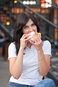 Hübsche junge brunettefrau, die hamburger im freien auf der straße isst.