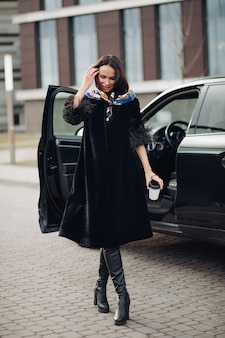 Hübsche junge dame, die einen modischen schwarzen mantel trägt, während sie kaffee hält und in der nähe des autos steht. konzept der modestadt