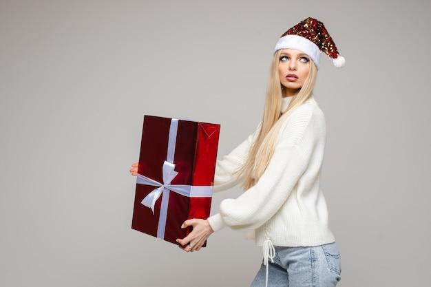 Hübsche junge dame, die im studio steht und große geschenkbox hält, lokalisiert auf grau