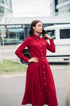 Hübsche junge dame, die rotes kleid trägt, während auf der straße mit auto und gebäude auf dem hintergrund aufwirft. stadtlebensstil