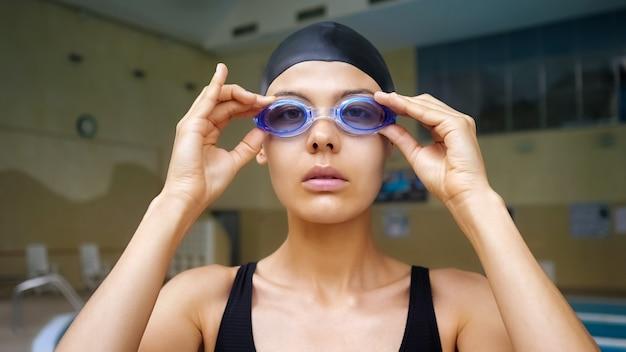 Hübsche junge dame in schwarzer badekappe und anzug setzt eine hellblaue schutzbrille auf, die bereit ist, im modernen lichtpool in der nähe zu trainieren