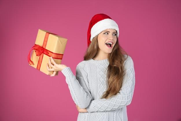Hübsche junge dame in weihnachtsmütze mit geschenkbox auf farbfläche