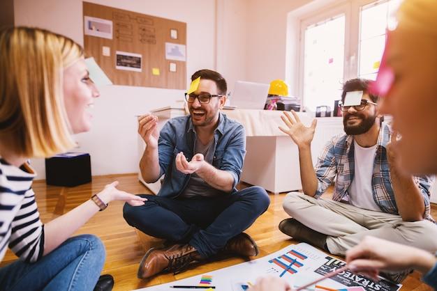 Hübsche junge designer-mitarbeiter, die ihre freizeit genießen und zusammengehörigkeit und teamgeist steigern, während sie im kreis auf dem boden des büros sitzen und spiele spielen
