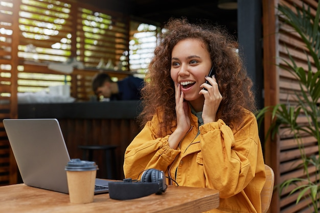 Hübsche junge dunkelhäutige lockige frau, die auf einer caféterrasse sitzt, im gelben mantel trägt, kaffee trinkt, glücklich erstaunt auf laptop schaut, mit einem freund am telefon spricht.