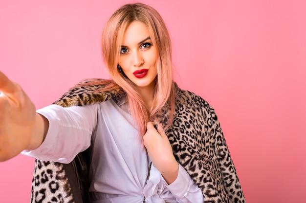 Hübsche junge elegante frau, die selfie am rosa hintergrund, trendige frisur und helles make-up macht, kuss macht und vor der kamera schaut.