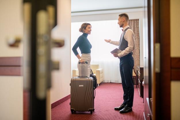 Hübsche junge elegante frau mit gepäck, das im hotelzimmer steht und mit dem träger spricht, der sie begrüßt