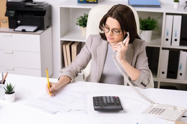 Hübsche junge elegante geschäftsfrau, die am schreibtisch im büro sitzt, kunden am telefon berät und notizen im dokument macht