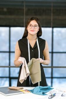 Hübsche junge elegante näherin oder modedesignerin in brillen, die mit textilmustern vor der kamera arbeiten