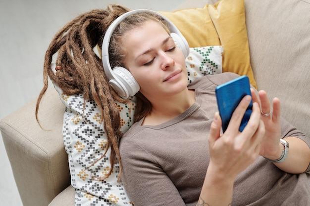 Hübsche junge erholsame frau mit dreadlocks, die musik in kopfhörern hören und in smartphone auf couch scrollen